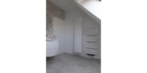 Salle de main avec radiateur mural et ranegements